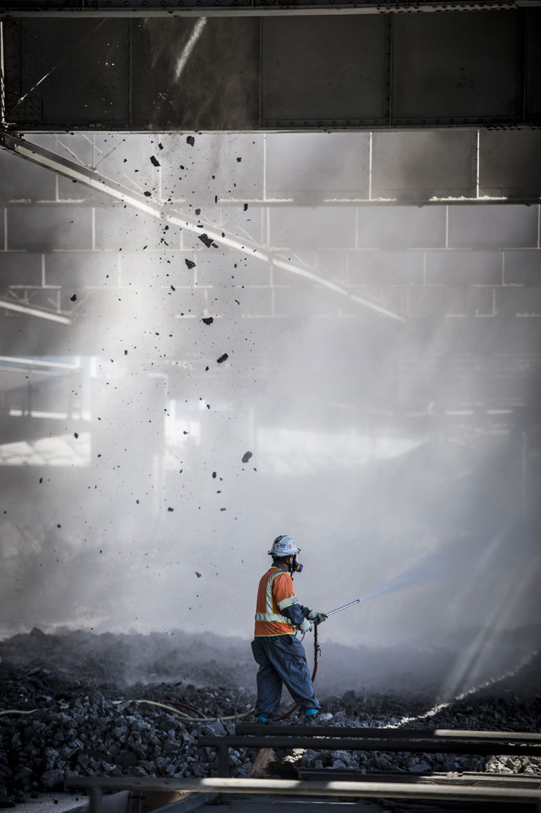 A construction demolition worker spays down dust.